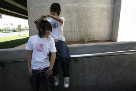 """A member of a group known as Pokemon combs his friend's hair outside a subway station in Santiago January 16, 2008. Pokemon, the popular Japanese series of cartoon characters whose name comes from the combination of the words """"pocket"""" and """"monster"""", is the most popular new wave among the Chilean youth, who dress and make up their hair accordingly and gather at afternoon reggaeton dance parties.Picture taken January 16, 2008.  REUTERS/Ivan Alvarado (CHILE)"""